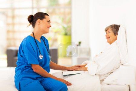 freundliche Krankenschwester besucht genesende Seniorin