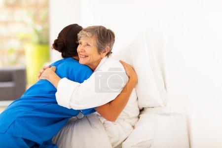Photo pour Heureuse femme âgée étreindre soignant sur lit - image libre de droit