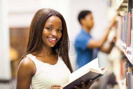 female african american university student reading book in library