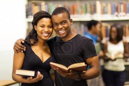 feliz africano americano pareja universitaria en biblioteca