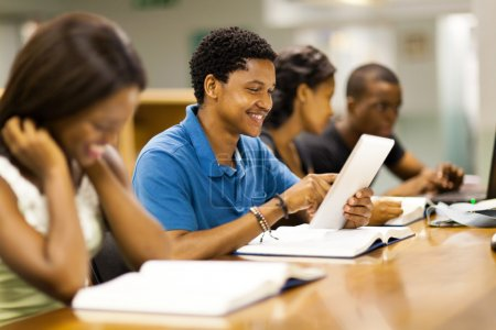 happy male african american college student using tablet computer