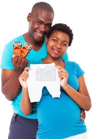Happy african american expecting couple holding baby clothes and shoes