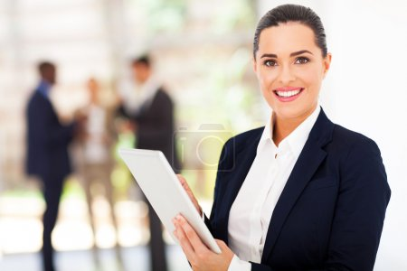 beautiful female corporate worker with tablet computer in office