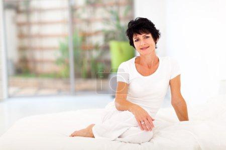 Foto de Hermosa mujer edad media sentado en la cama - Imagen libre de derechos