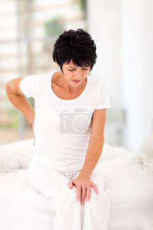 Woman sitting on bed having back pain