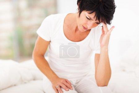 Foto de Mujer edad media sentada en la cama y tener dolor de cabeza - Imagen libre de derechos