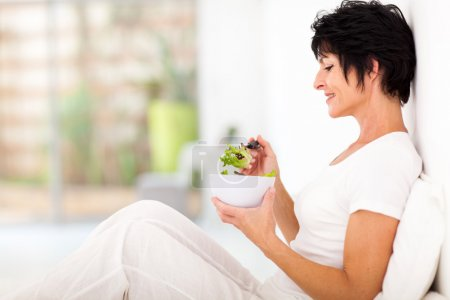 Photo for Elegant middle aged woman sitting on bed and eating salad - Royalty Free Image