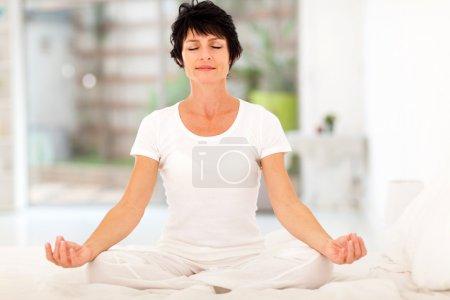 Photo pour Belle femme d'âge moyen méditation sur le lit à la maison - image libre de droit