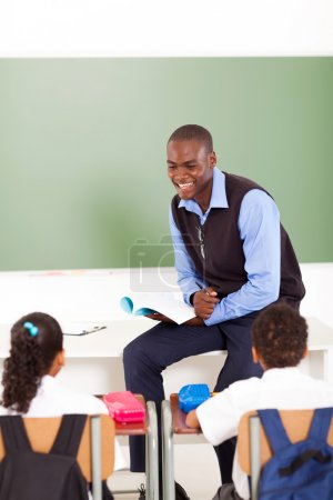 Male african primary school teacher teaching in classroom