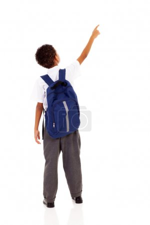 Little schoolboy with schoolbag pointing at empty copy space
