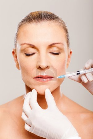 Mature woman receiving lips injection