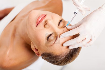 Cosmetic injection to senior woman