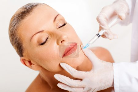 Middle aged woman receiving chin injection