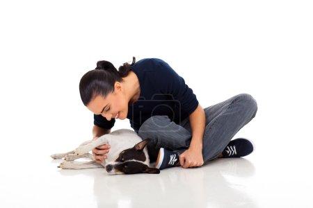 Photo pour Femme occasionnelle assise sur le sol et jouant avec son chien - image libre de droit