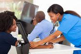 african medical nurse measuring patient's blood pressure