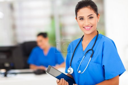 Photo for Attractive young female nurse holding tablet computer at workplace - Royalty Free Image