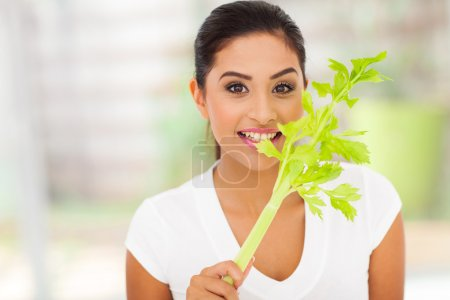 Photo for Young female vegetarian biting celery's leaves - Royalty Free Image