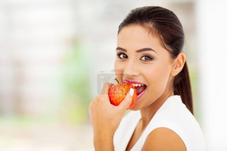 Photo for Beautiful young woman eating an apple - Royalty Free Image