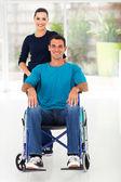 homme handicapé et bienveillante femme à la maison