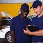 Постер, плакат: Happy auto mechanics going through checklist