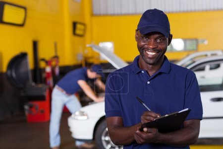 african american male vehicle mechanic writing report