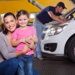 Happy young mother and little daughter in garage w...