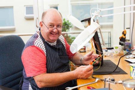 senior electrician checking circuit board