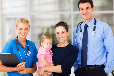 woman holding her baby standing with doctor and female nurse