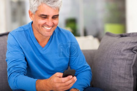 Photo for Cheerful middle aged man reading emails on smart phone - Royalty Free Image