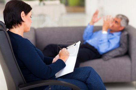 Photo for Middle aged female psychologist making note while patient talking - Royalty Free Image