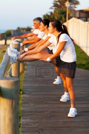 family stretching at the beach before jogging
