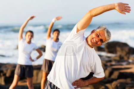Photo for Happy mid age man exercising at the beach with his family - Royalty Free Image