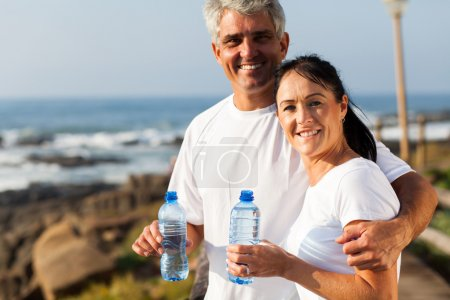 fit mature couple drinking water