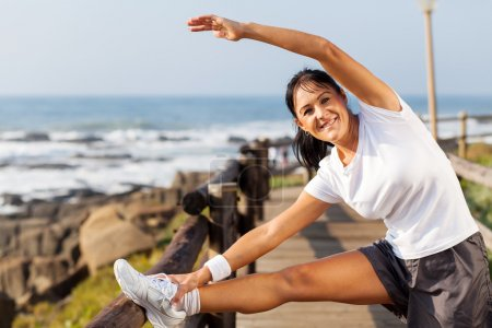 Photo for Fit mature woman doing morning stretching at the beach in the morning - Royalty Free Image