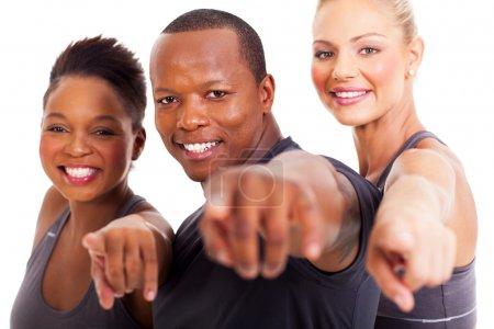 Photo pour Souriant groupe d'instructeurs de gym pointant à l'appareil photo sur fond blanc - image libre de droit