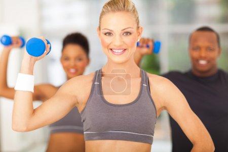 Photo pour Groupe de joyeux exercice dans la salle de gym avec haltères - image libre de droit