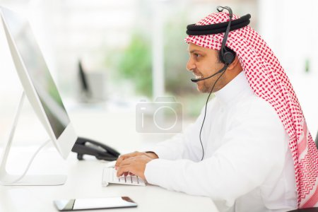 Photo for Smiling middle eastern businessman working on a computer with headset - Royalty Free Image