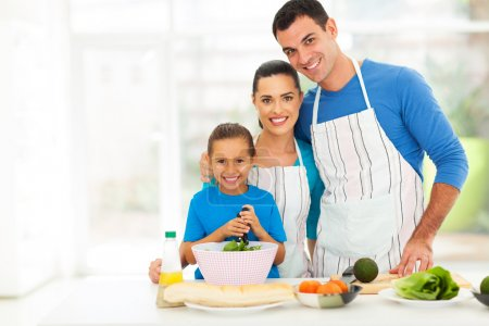 adorable young family cooking at home