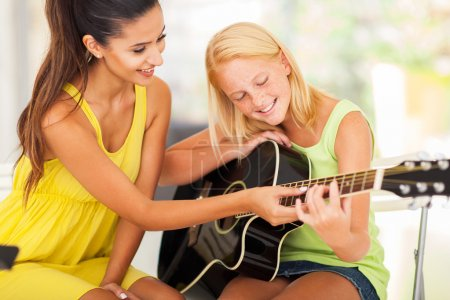Photo for Smiling beautiful music teacher tutoring young girl to play guitar - Royalty Free Image