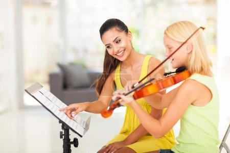 Preteen girl play violin under teacher's instructions