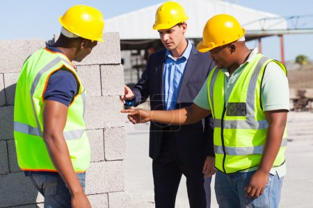 Construction workers with their manager checking bricks