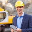 Happy manager in mining site holding ore...