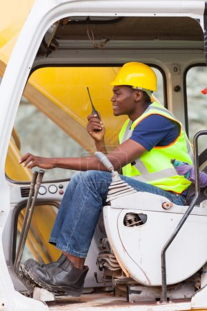 afro american man operates excavator