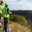 Two male surveyors working at mining site...