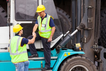 Forklift driver handshaking with colleague