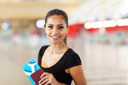 Photo pour Joyeuse jeune femme d'affaires avec passeport et billet d'avion à l'aéroport - image libre de droit