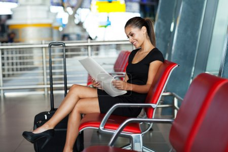 Young businesswoman reading newspaper at airport