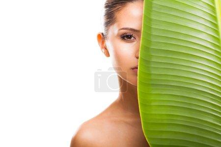 Photo pour Grande feuille vert ombrage demi visage de belle femme sur fond blanc - image libre de droit