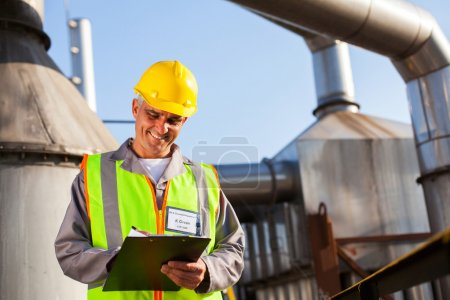 Petrochemical engineer recording technical data on clipboard