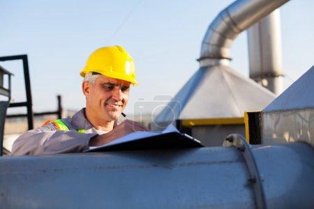 Photo pour Technicien de l'industrie chimique du pétrole d'âge moyen travaillant à l'extérieur - image libre de droit